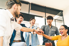 stock image of  multiethnic diverse group of happy colleagues join hands together. creative team, casual business coworker, or college students