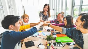 stock image of  multiethnic diverse group of office coworker, business partner fist bump in modern office. colleague partnership teamwork concept