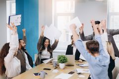stock image of  multiethnic diverse happy team celebrate project success throw paper up together. corporate community, college graduation, startup