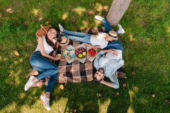 stock image of  multiethnic family eating and drinking while resting on plaid at picnic