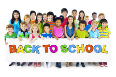 stock image of  multiethnic group of children with bcak to school placard