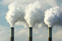 stock image of  multiple coal fossil fuel power plant smokestacks emit carbon dioxide pollution