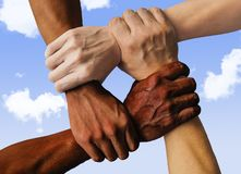 stock image of  multiracial group with black african american caucasian and asian hands holding each other wrist in tolerance unity love and anti