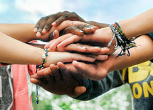 stock image of  multiracial teen friends joining hands together in cooperation