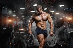 stock image of  muscular athletic bodybuilder fitness model posing after exercises in gym