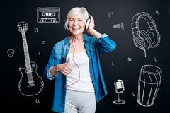 stock image of  positive senior woman putting her thumb up while listening to music