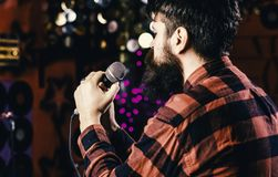 stock image of  musician with beard singing song in karaoke, rear view. man in checkered shirt holds microphone, singing song, karaoke