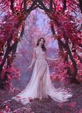 stock image of  mysterious attractive lady in a long light luxury dress in a magical pink forest, gate to the fairy-tale world, cute