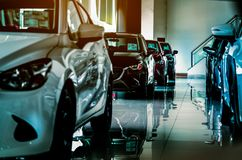 stock image of  new luxury car parked in modern showroom for sale. car dealership office. car retail shop.