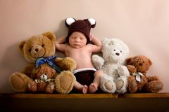 stock image of  newborn baby boy wearing a brown knitted bear hat and pants, sleeping on a shelf