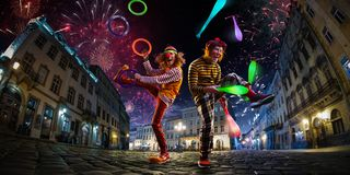 stock image of  night street circus performance whit two clowns, jugglerfestival city background. fireworks and celebration atmosphere.wide engle