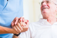 stock image of  nurse holding hand of senior man in rest home