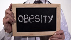 stock image of  obesity written on blackboard in doctor hands, healthy nutrition recommendations
