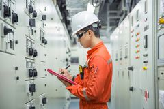stock image of  electrical and instrument technician logging data in electrical switch gear room.