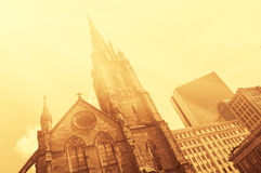 stock image of  old church in front of modern glass-and-steek buildings of boston downtown