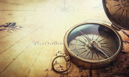 stock image of  old compass on vintage map. adventure stories background.