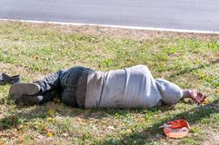 stock image of  old dirty drunk or drug addict barefoot homeless or refugee man sleeping on the grass in the street social documentary concept