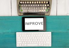 stock image of  old typewriter keyboard and modern computer keyboard and tablet pc with word & x22;improve& x22;