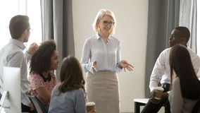 stock image of  old woman mentor coach training multicultural interns group in office