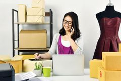 stock image of  online business, young asian woman work at home for e-business commerce, small business owner checking and packing online order.