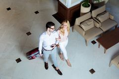 stock image of  overhead view of happy couple of travelers walking with luggage