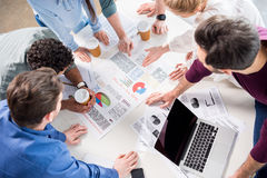 stock image of  overhead view of professional businesspeople discussing and brainstorming together on workplace in office