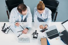 stock image of  overhead view of scientific researchers in white coats using tablet together at workplace