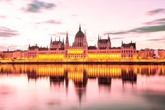 stock image of  parliament and riverside in budapest hungary during sunrise. famous landmark in budapest.