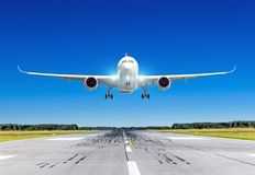 stock image of  passenger airplane with bright landing lights landing at in good clear weather with a blue sky on a runway.