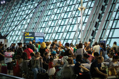 stock image of  passengers waiting at crowded departure gate after delay, shanghai pudong airport, china.