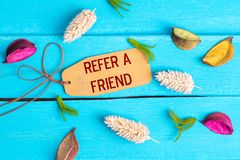 stock image of  refer a friend text on paper tag