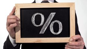 stock image of  percent sign drawn on blackboard in businessman hands, deposit interest rate