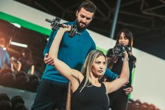 stock image of  personal trainer helping woman working with dumbbells
