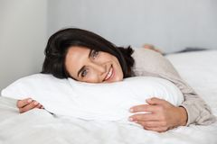 stock image of  photo of joyful woman 30s smiling, while lying in bed with white linen at home
