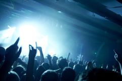 stock image of  photo of people having fun at rock concert, fans applauding to famous music band, rock star on the stage.