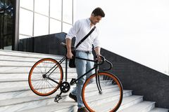 stock image of  photo of smiling man 30s wearing formal clothing, walking downstairs with bicycle on city street