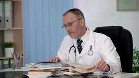 stock image of  physician reading medical books searching information about rare disease science