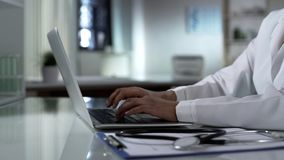 stock image of  physician typing on laptop, patients medical record, healthcare technology