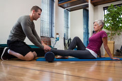 stock image of  physiotherapist giving physical therapy of leg to senior patient