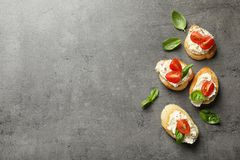 stock image of  pieces of baguette with tasty cream cheese and tomatoes on gray table, flat lay.