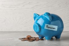 stock image of  piggy bank with word pension and coins on table