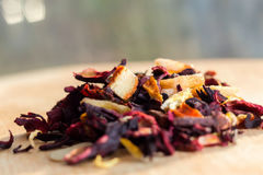 stock image of  pile of fruit tea with petals and dry fruit .the composition of the heap of tea leaves and dried hibiscus flower located on a wood