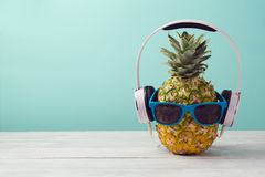 stock image of  pineapple with headphones and sunglasses on wooden table over mint background. tropical summer vacation and beach party.