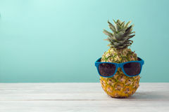 stock image of  pineapple with sunglasses on wooden table over mint background. tropical summer vacation and beach party
