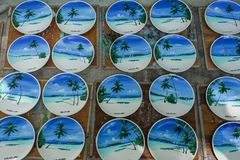 stock image of  plenty of wooden souvenirs with landscapes of maldives on it