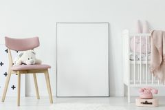stock image of  plush toy on pink chair next to poster with mockup in baby`s roo