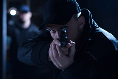 stock image of  policeman aiming gun during intervention