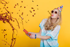 stock image of  portrait of funny blond woman in birthday hat and red confetti on yellow background. celebration and party.