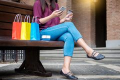 stock image of  portrait of a happy shopper paying online with credit card through smartphone with bags in a mall.