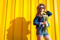 stock image of  portrait of hipster girl wearing glasses and hat with flowers against yellow background. summer outfit. fashion. space